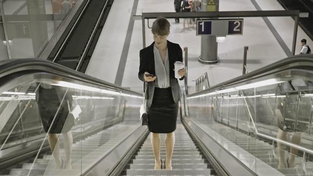 berliner geschäftsfrau steigt auf rolltreppe im bahnhof auf - rolltreppe stock-videos und b-roll-filmmaterial
