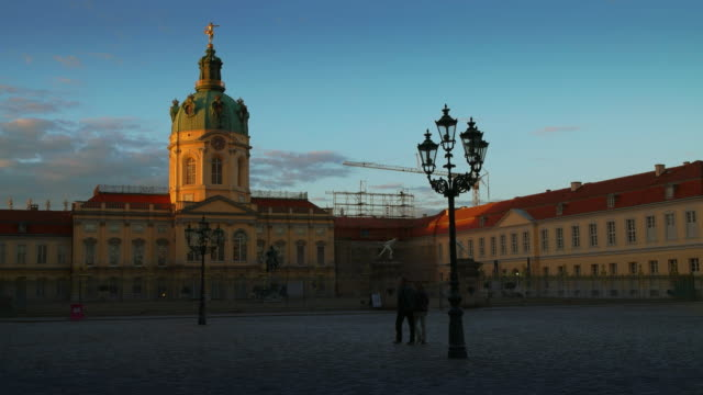 berlin charlottenburg palace with walking couple at historic landmark, germany, evening - charlottenburg palace stock videos & royalty-free footage