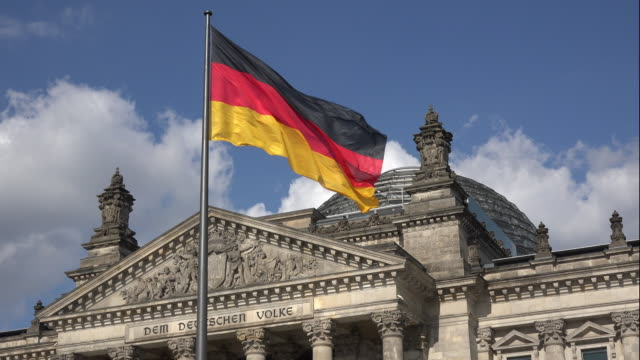 stockvideo's en b-roll-footage met berlin cinemagraphs, german flag in front of the reichstag building - duitsland