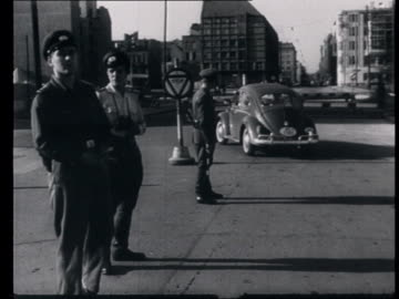 vidéos et rushes de construction of the wall , everyday life behind the wall : cars going trough checkpoint, american soldiers patrolling. - 1961