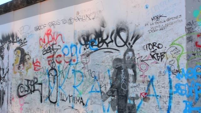 vídeos y material grabado en eventos de stock de berlin germany remaining part of berlin wall with artists painting in downtown city at east side gallery - figura femenina