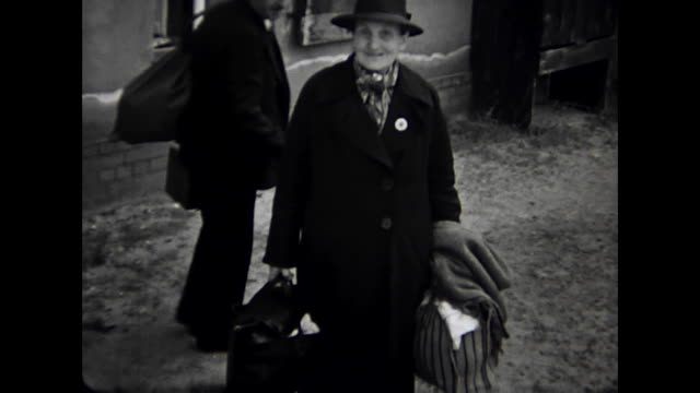 berlin in times of world war ii, people leaving air-raid shelter after airstrike alert, old woman with many bags looks friendly and happy to the... - 空爆点の映像素材/bロール