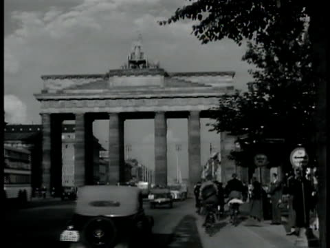 vidéos et rushes de berlin map. vs traffic under brandenburg gate. soldiers at nazi rally altes museum bg. vs german soldiers marching in rally w/ nazi flags large... - 1939