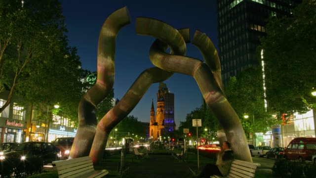 vídeos y material grabado en eventos de stock de time lapse wide shot berlin sculpture with traffic going by on tauentzienstrasse and kaiser wilhelm memorial church in background from dusk to night, berlin, germany - iglesia conmemorativa del emperador guillermo