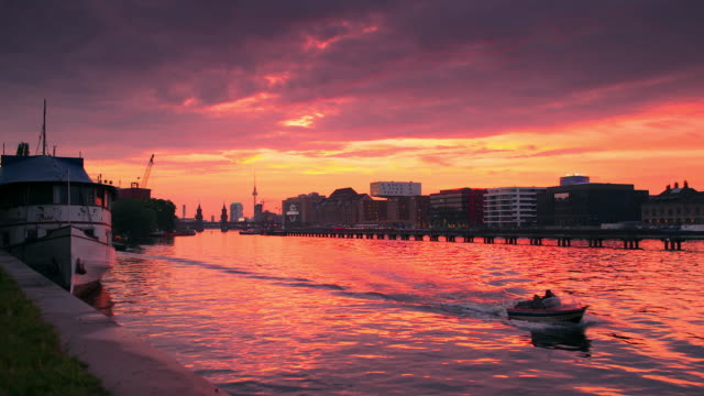 Berlin Spree Skyline City in Summer with Boat and dramatic colorful Sunset