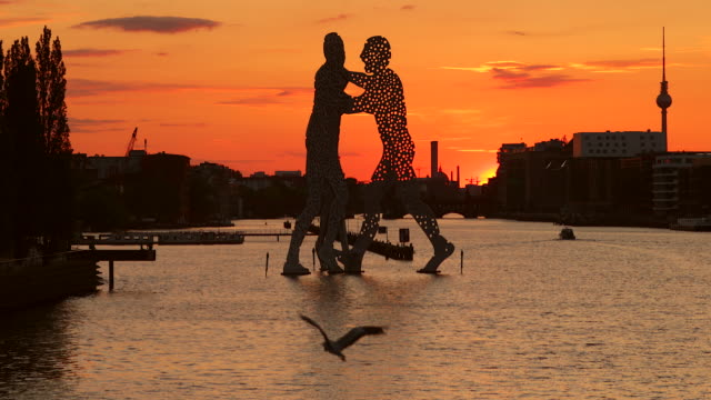 berlin spree skyline in summer with flying bird and sunset - establishing shot stock-videos und b-roll-filmmaterial
