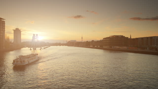 berlin spree skyline in summer with ship and sunset - establishing shot stock-videos und b-roll-filmmaterial