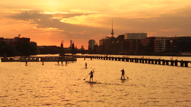 berlin summer sunset skyline with paddle surfing people - スプリー川点の映像素材/bロール