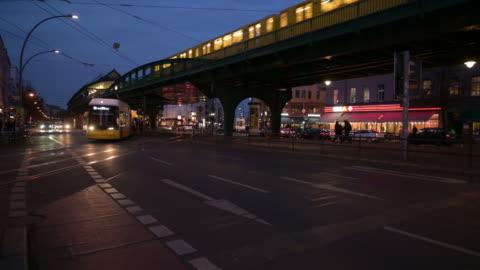 berlin urban night street scene with traffic trains and lights steady cam dolly shot - night stock-videos und b-roll-filmmaterial