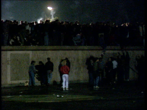 Berlin Wall border opening reactions Brandenburg Gate Illuminated Brandenburg Gate as people crowded around Brandenburg gate as street sign in...