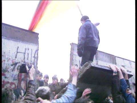 vídeos de stock, filmes e b-roll de berlin wall collection t11118901 the wall starts to crumble e german guards on top of wall west germans beginning to pull down wall sprayed by... - muro