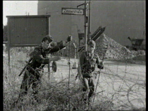 berlin wall collection tx 1381961 barbed wire erected west berlin group of west berliners watch east german soldiers put up barbed wire barriers... - 1961 stock videos & royalty-free footage
