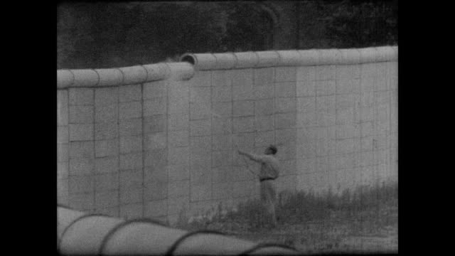 stockvideo's en b-roll-footage met of berlin wall / east german worker sprays white paint onto wall to provide a bright nighttime background, discouraging further escape attempts /... - berlijnse muur
