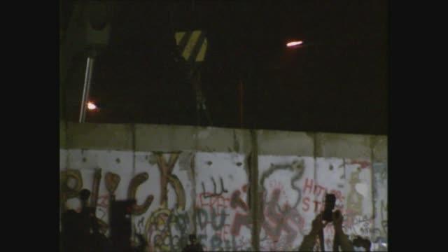 stockvideo's en b-roll-footage met gvs of west berlin; west germany: west berlin: ext / night gvs crane lifts section of wall as crowd holding sparklers cheer; - berlijnse muur