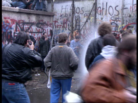 berlin wall sections of wall pulled down west germany west berlin ext east german officer walking along top of wall past line of soldiers as noisy... - sledgehammer stock videos & royalty-free footage