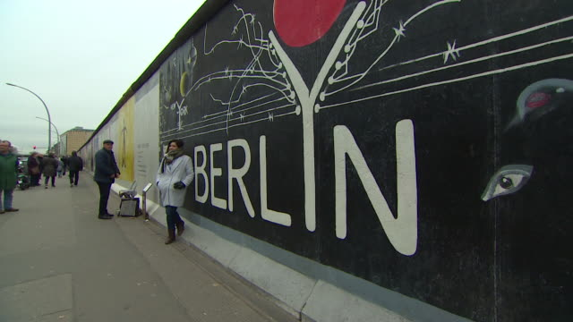 Berlin Wall tourist walking past and having photos taken