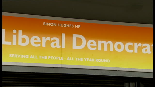 stockvideo's en b-roll-footage met ext reporter to camera simon hughes name and lib dem sign above constituency office general view of liberal democrat constituency office travelling... - street name sign