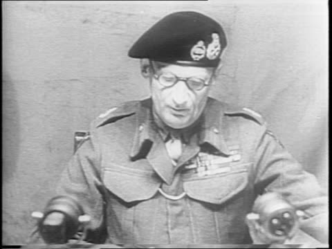 bernard montgomery with admiral hansgeorg von friedeburg and german soldiers/ montgomery seated in tent and speaks on procedure of signing... - arrendersi video stock e b–roll