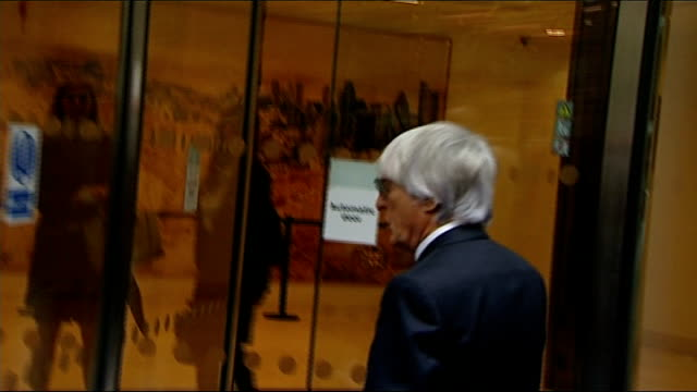 bernie ecclestone court case; england: london: high court: ext bernie ecclestone arriving at court and through revolving doors as appears to become... - bernie ecclestone stock videos & royalty-free footage