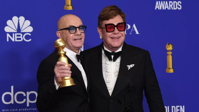 bernie taupin and elton john pose in the press room with the award for best original song motion picture during the 77th annual golden globe awards... - the beverly hilton hotel stock-videos und b-roll-filmmaterial