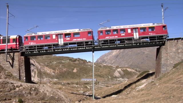 bernina express crossing the upper berninabach bridge - kulturen stock-videos und b-roll-filmmaterial