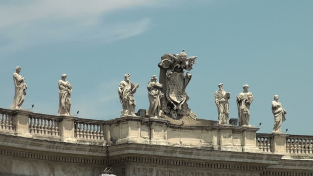 Bernini's colonnade, saints, and tourists in St. Peter's Square, Rome