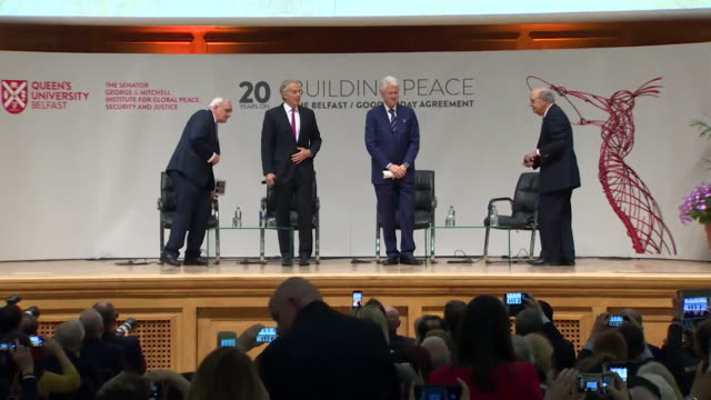 bertie ahern tony blair bill clinton and george mitchell arriving on stage at queen's university belfast on the 20th anniversary of the good friday... - バーティ アハーン点の映像素材/bロール