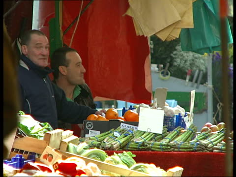 berwick street market general views; various bags, hats on display at market stand / more of fruit and veg stall / people along up street past... - sea bass stock videos & royalty-free footage