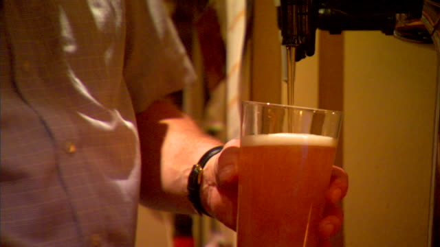 ms male filling pint glass w/ draft beer from draught tap handing glass out of frame iconic bitter pale ale lager pilsner english public house... - pilsner stock videos & royalty-free footage
