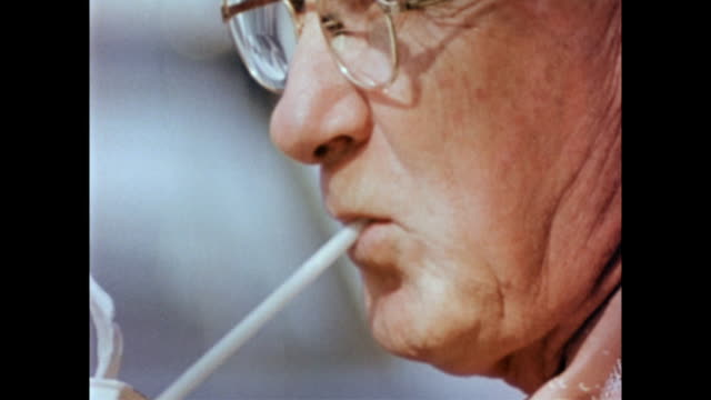 bespectacled older man wearing hat and drinking out of straw man drinking through a straw on january 01 1958 - anno 1958 video stock e b–roll