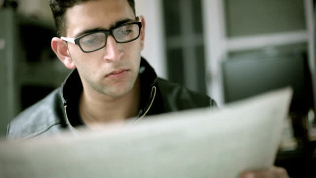 Bespectacled young man reading newspaper.
