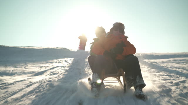 best ager couple tobogganing