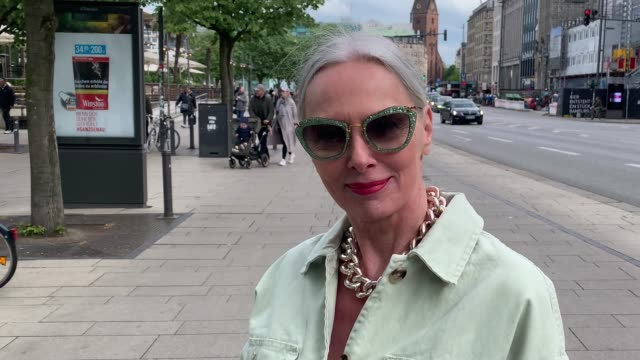 best ager model and influencer petra van bremen wearing a mint green denim jacket by zara, a pink pleated skirt with animal and floral print by h&m,... - street style点の映像素材/bロール