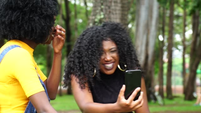 best friends doing a video calling in the park - adolescence stock videos & royalty-free footage