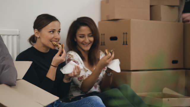 bästa vänner äter pizza medan du flyttar hem - flyttlåda bildbanksvideor och videomaterial från bakom kulisserna