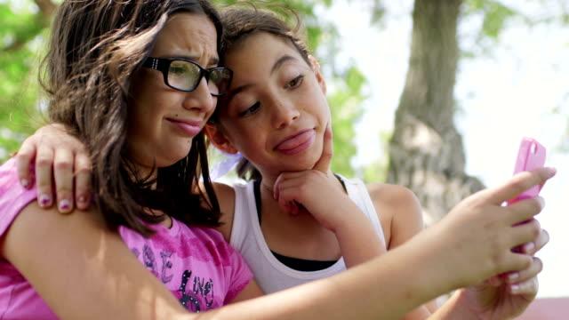 stockvideo's en b-roll-footage met best friends making silly faces at smart phone clip 1 - selfie