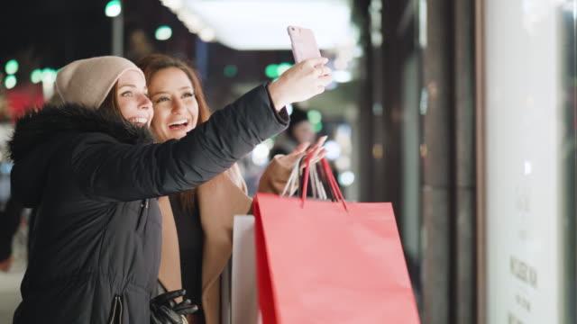 Beste vrienden een selfie nemen terwijl venster-winkelend voor kerstvakantie