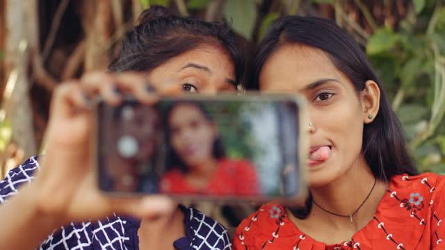 vídeos de stock, filmes e b-roll de best friends taking selfies in a public park - smart