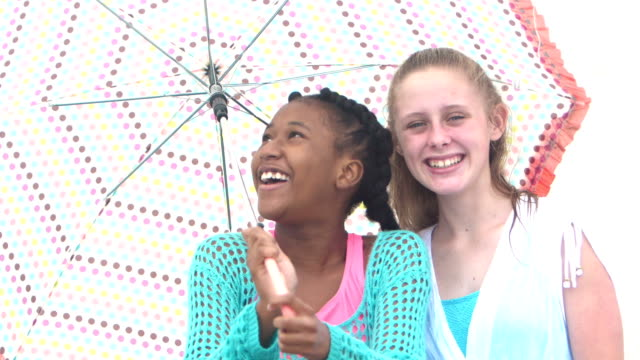 best friends under an umbrella at the beach - 12 13 years stock videos & royalty-free footage