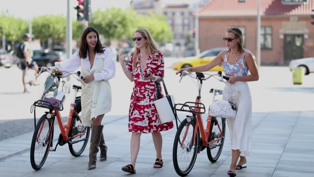 bettina looney wearing beige dress white oversized button shirt brown boots stella von senger wearing red dress with white print bucket bag and a... - kopenhagen stock-videos und b-roll-filmmaterial