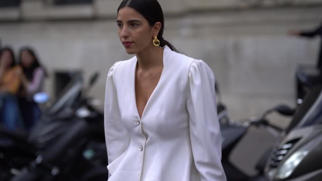 bettina looney wears a white ruffled jacket blue large jeans green shoes a brown bag outside elie saab during paris fashion week womenswear spring... - modewoche stock-videos und b-roll-filmmaterial