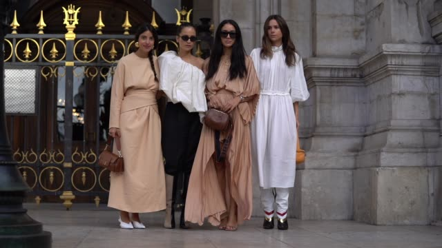bettina looney wears earrings a beige long dress a brown bag white pointy pumps anna rosa vitiello wears sunglasses a gathered flowing asymmetric... - knee highs stock videos and b-roll footage
