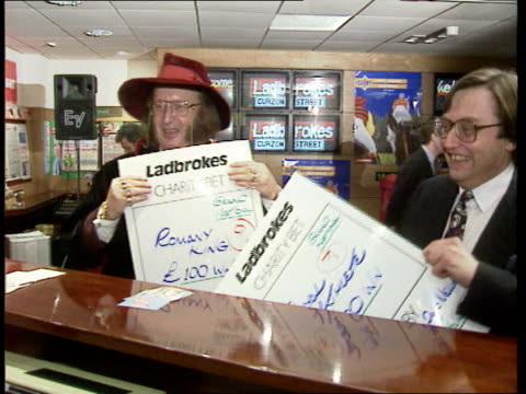 stockvideo's en b-roll-footage met betting shops late opening england london john mccririck and david mellor mp in betting shop holding extra large ladbrokes betting slips for grand... - john mccririck