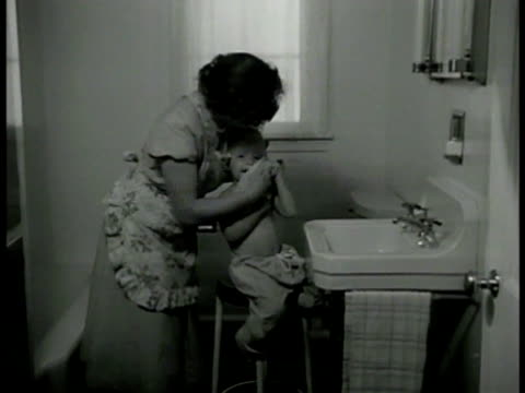 WIFE 'BETTY' MS 'Betty' cleaning toddler son 'Gary' on stool by sink in bathroom MS Gary sitting on stool being cleaned w/ wet towel Motherly care...