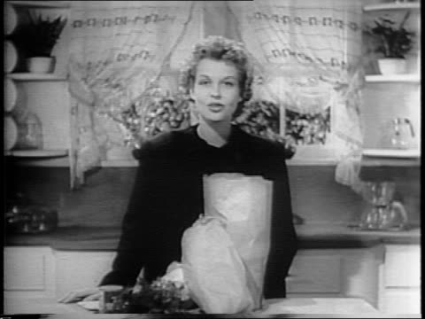 betty field talks about food rations in war film bulletin number 4 / field in kitchen with bag of groceries - psa stock videos & royalty-free footage