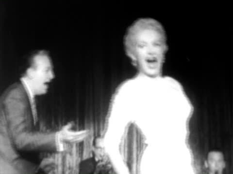 Betty Grable dancing performing with Harry James and his Orchestra with famed drummer Buddy Rich on the traps / Betty Grable stepping to microphone...