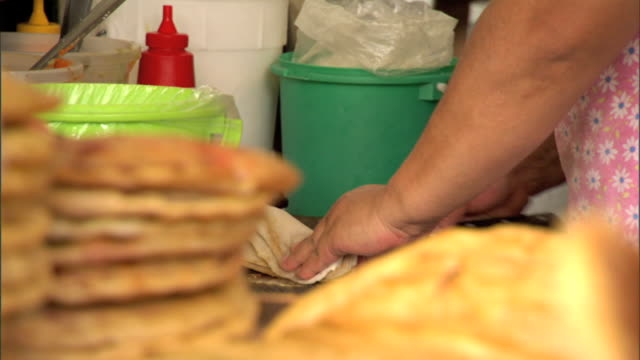 between mcu unidentifiable female hands cutting, stuffing & preparing gordita & stack of tortillas in fg. mexican food, cuisine - tortilla flatbread stock videos & royalty-free footage