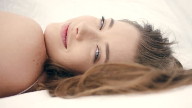 between the sheets. dreamy woman flirting with camera - sheet stock videos & royalty-free footage