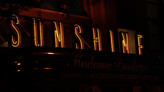 Between traffic moving along Houston Street and illuminated yellow neon 'Sunshine' sign on facade over entrance of movie theater
