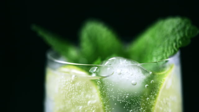 cu beverage garnished with mint leaves and lime slices - mint leaf culinary stock videos and b-roll footage